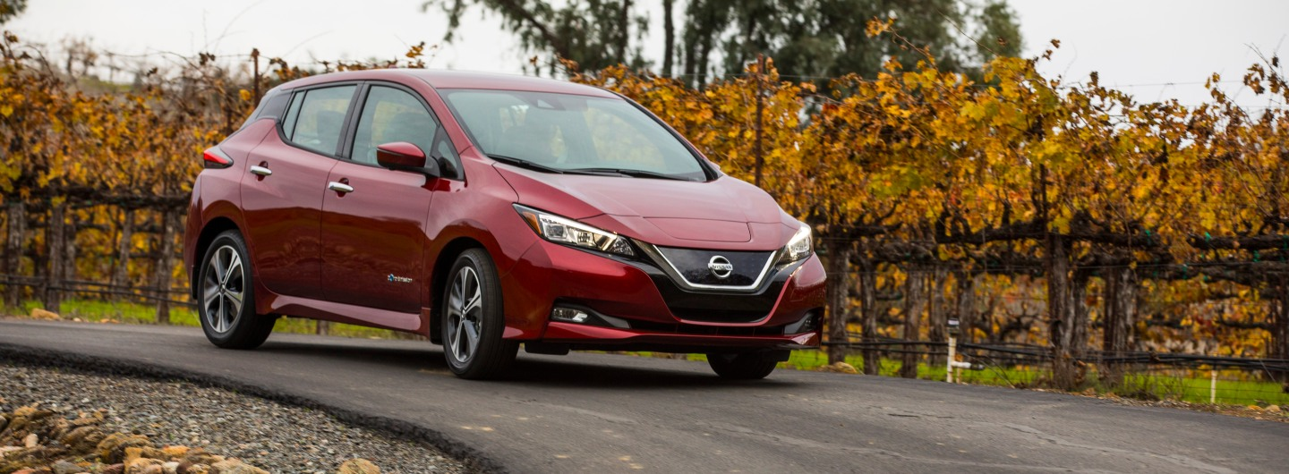 A red nissan leaf drives through a vineyard on a curving road